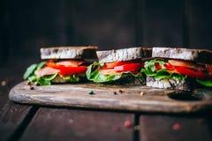 Σάντουιτς με το καφετί ψωμί σίκαλης, τις ώριμες ντομάτες, τα αγγούρια και τα ψάρια τόνου Στοκ Εικόνες