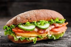 Σάντουιτς με το κοτόπουλο, το τυρί μπέϊκον και τα λαχανικά Στοκ Εικόνες