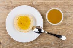Σάντουιτς με το μέλι στο πιάτο, το κουταλάκι του γλυκού και το κύπελλο με το μέλι Στοκ Εικόνα