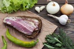Σάντουιτς με το μπέϊκον, το σκόρδο, το κρεμμύδι και το πιπέρι Στοκ εικόνα με δικαίωμα ελεύθερης χρήσης