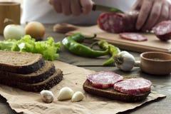 Σάντουιτς με το λουκάνικο και τεμαχισμένο †‹â€ ‹στο υπόβαθρο Στοκ Εικόνα