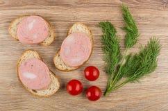 Σάντουιτς με το λουκάνικο, το κεράσι ντοματών και τον άνηθο στον ξύλινο πίνακα Στοκ Εικόνες