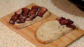Σάντουιτς με το τηγάνισμα του μπέϊκον απόθεμα βίντεο