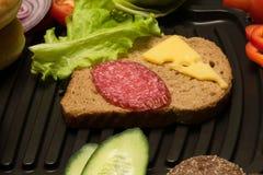 Σάντουιτς με το τυρί και λουκάνικο, λαχανικά γύρω από τη σχάρα Στοκ Φωτογραφίες