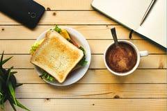 Σάντουιτς με το τυρί, τη σαλάτα και το κρέας και το φλιτζάνι του καφέ στοκ φωτογραφίες