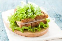 Σάντουιτς με το τυρί, το ζαμπόν και τη σαλάτα σε έναν πίνακα Στοκ φωτογραφία με δικαίωμα ελεύθερης χρήσης