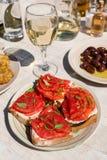 Σάντουιτς με το τυρί φέτας, φρέσκες ντομάτες, φύλλα βασιλικού ως appertizer στον εξυπηρετούμενο πίνακα στην ελληνική ταβέρνα Στοκ Εικόνες