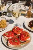 Σάντουιτς με το τυρί φέτας, φρέσκες ντομάτες, φύλλα βασιλικού ως appertizer στον εξυπηρετούμενο πίνακα στην ελληνική ταβέρνα Στοκ Φωτογραφία