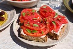 Σάντουιτς με το τυρί φέτας, φρέσκες ντομάτες, φύλλα βασιλικού ως appertizer Στοκ Φωτογραφίες