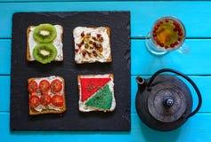 Σάντουιτς με το φλυτζάνι του τσαγιού και μαύρο teapot στοκ φωτογραφία