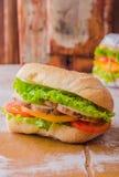 Σάντουιτς με το ψημένο κοτόπουλο, τη σαλάτα φύλλων και τις ντομάτες στο ξύλινο baskgraund Εκλεκτική εστίαση Στοκ Εικόνα