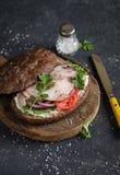 Σάντουιτς με το ψημένο χοιρινό κρέας, το μαλακό τυρί, τις ντομάτες και το arugula στον ξύλινο τέμνοντα πίνακα στο σκοτεινό υπόβαθ Στοκ Εικόνες