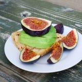 Σάντουιτς με το ψημένο ψωμί, τα πορφυρά σύκα και το αβοκάντο στοκ εικόνες