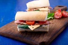 Σάντουιτς με το jamon, arugula, ντομάτες, τυρί στο ξύλινο μπλε υπόβαθρο πινάκων αγροτικός Στοκ εικόνα με δικαίωμα ελεύθερης χρήσης
