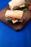 Σάντουιτς με το jamon, arugula, ντομάτες, τυρί στο ξύλινο μπλε υπόβαθρο πινάκων αγροτικός Δύο Στοκ εικόνα με δικαίωμα ελεύθερης χρήσης