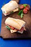 Σάντουιτς με το jamon, arugula, ντομάτες, τυρί στο ξύλινο μπλε υπόβαθρο πινάκων αγροτικός Δύο Στοκ φωτογραφία με δικαίωμα ελεύθερης χρήσης