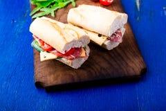 Σάντουιτς με το jamon, arugula, ντομάτες, τυρί στο ξύλινο μπλε υπόβαθρο πινάκων αγροτικός Δύο Στοκ εικόνες με δικαίωμα ελεύθερης χρήσης