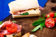Σάντουιτς με το jamon, arugula, ντομάτες, τυρί στο ξύλινο μπλε υπόβαθρο πινάκων αγροτικός Στοκ Φωτογραφία