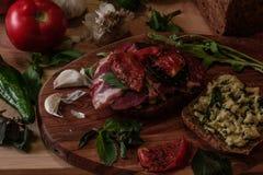 σάντουιτς με το pesto, τις ξηραμένες από τον ήλιο ντομάτες, το βασιλικό, το arugula και το καπνισμένο βόειο κρέας Στοκ Φωτογραφίες