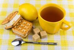 Σάντουιτς μπισκότων, φλυτζάνι του τσαγιού, λεμόνι και ζάχαρη Στοκ Φωτογραφίες