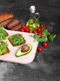 Σάντουιτς σε ένα επιτραπέζιο υπόβαθρο Ψωμί, ντομάτες, αβοκάντο και arugula κοντά σε ένα τέμνον γραφείο υγιής τρόπος ζωής έννοιας Στοκ φωτογραφία με δικαίωμα ελεύθερης χρήσης