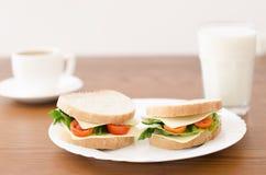 Σάντουιτς σε ένα πιάτο και ένα ποτήρι του γάλακτος, φλιτζάνι του καφέ σε ένα ξύλινο υπόβαθρο Στοκ φωτογραφία με δικαίωμα ελεύθερης χρήσης