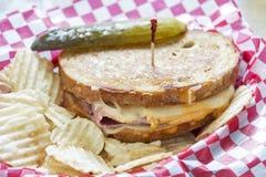 Σάντουιτς του Reuben ύφους Deli με τα τσιπ πατατών και ένα τουρσί Στοκ εικόνα με δικαίωμα ελεύθερης χρήσης
