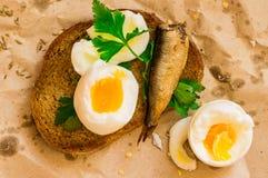 Σάντουιτς τροφίμων οδών με το αυγό και σαρδέλλες σε χαρτί Στοκ εικόνα με δικαίωμα ελεύθερης χρήσης