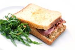 Σάντουιτς φρυγανιάς με το ζαμπόν, το τυρί, το κρεμμύδι και τη σαλάτα στο άσπρο πιάτο, που απομονώνεται στο άσπρο υπόβαθρο Στοκ εικόνα με δικαίωμα ελεύθερης χρήσης