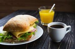 Σάντουιτς Chiabatta, φλιτζάνι του καφέ και χυμός από πορτοκάλι Στοκ εικόνες με δικαίωμα ελεύθερης χρήσης