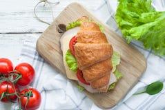 Σάντουιτς Croissant με το μπέϊκον, το τυρί, το μαρούλι και την ντομάτα Στοκ Εικόνα