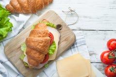 Σάντουιτς Croissant με το μπέϊκον, το τυρί, το μαρούλι και την ντομάτα Στοκ φωτογραφία με δικαίωμα ελεύθερης χρήσης