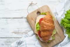 Σάντουιτς Croissant με το μπέϊκον, το τυρί, το μαρούλι και την ντομάτα Στοκ Εικόνες