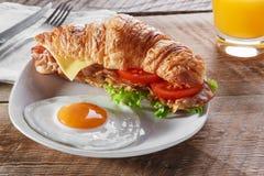 Σάντουιτς croissant με το τηγανισμένα πρόγευμα και το αυγό ντοματών τυριών μπέϊκον Στοκ Φωτογραφία