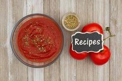 Σάλτσα ντοματών στο σαφές κύπελλο με oregano το καρύκευμα και την κόκκινη άμπελο ώριμα Στοκ Εικόνες