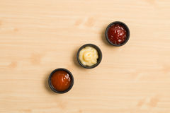 Σάλτσα τρία στο μαύρο κύπελλο στο ξύλινο υπόβαθρο Στοκ Φωτογραφίες