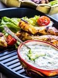 Σάλτσα Tzatziki Σάλτσα Tzatziki Tzatziki που ντύνει με τα ψημένο στη σχάρα πόδια κοτόπουλου και το φρέσκο λαχανικό, το φύλλο μαρο Στοκ Φωτογραφίες