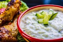 Σάλτσα Tzatziki Σάλτσα Tzatziki Tzatziki που ντύνει με τα ψημένο στη σχάρα πόδια κοτόπουλου και το φρέσκο λαχανικό, το φύλλο μαρο Στοκ Εικόνα