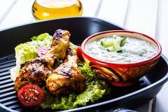 Σάλτσα Tzatziki Σάλτσα Tzatziki Tzatziki που ντύνει με τα ψημένο στη σχάρα πόδια κοτόπουλου και το φρέσκο λαχανικό, το φύλλο μαρο Στοκ εικόνα με δικαίωμα ελεύθερης χρήσης