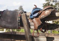 Σέλα και saddle-cloth σε ένα ξύλινο πλαίσιο στοκ φωτογραφία με δικαίωμα ελεύθερης χρήσης