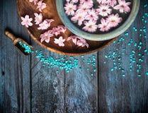Σέσουλα με το αλατισμένο κύπελλο θάλασσας και λουλούδια στο νερό στον μπλε ξύλινο πίνακα, υπόβαθρο SPA Στοκ φωτογραφία με δικαίωμα ελεύθερης χρήσης