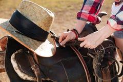 Σέλα που προετοιμάζεται για την ιππασία από τη νέα γυναίκα cowgirl Στοκ φωτογραφία με δικαίωμα ελεύθερης χρήσης