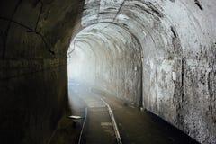 Σήραγγα φορτίου στην εγκαταλειμμένη σοβιετική αποθήκη με το σιδηρόδρομο Γυρίστε τη σήραγγα Φως από τη στροφή Στοκ Φωτογραφίες