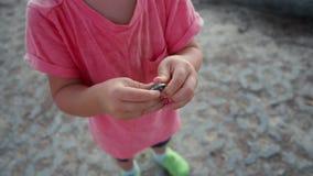 Σίδηρος γύρω από το νόμισμα στα χέρια του παιδιού απόθεμα βίντεο