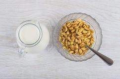 Σίτος με το μέλι στο κύπελλο, το κουταλάκι του γλυκού και την κανάτα του γάλακτος Στοκ Φωτογραφίες