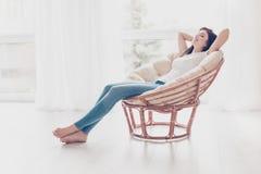Σαββατοκύριακα τελικά! Το χαλαρωμένο κορίτσι brunette κάθεται στο σύγχρονο cha στοκ εικόνα με δικαίωμα ελεύθερης χρήσης