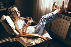 Σαββατοκύριακα τελικά Γυναίκα στο τζιν παντελόνι που χαλαρώνει με το φλυτζάνι του τσαγιού στην πολυθρόνα στο σπίτι, αφηρημάδα Κορ Στοκ Εικόνες