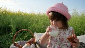 Σαββατοκύριακο στο πικ-νίκ, το κορίτσι στο λιβάδι λουλουδιών με τις ζύμες και το γάλα, ευτυχές χαρούμενο παιδί, καλό κορίτσι στο  απόθεμα βίντεο
