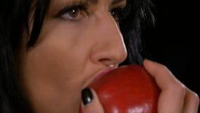 Σαγηνευτική γυναίκα που δαγκώνει ένα νόστιμο κόκκινο μήλο απόθεμα βίντεο