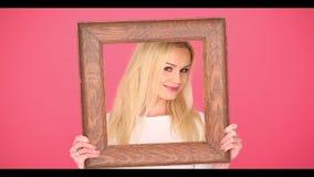 Σαγηνευτική γυναίκα που πλαισιώνει το πρόσωπό της σε ένα πλαίσιο απόθεμα βίντεο